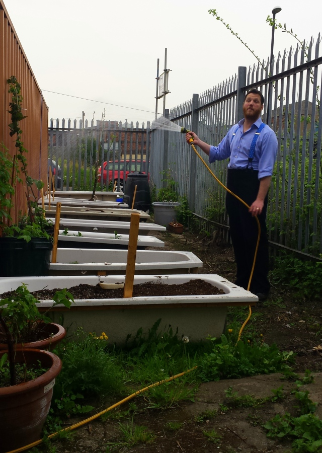 The Artistic Director waters the garden